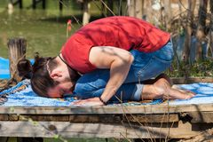 Young man practice yoga summer day by the lake child poses for relaxation. Young man practice yoga summer day by the lake child pose for relaxation and resting stock images