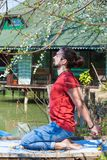 Young man practice yoga summer day by the lake stretching. Side view full body shot cg royalty free stock images