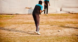 Young man practicing around a field. A young man is practicing around a cricket isolated unique photograph stock images