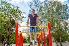 Young man is practicing on a horizontal bar Royalty Free Stock Photography