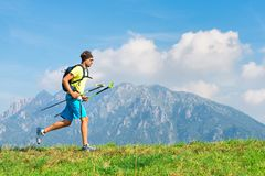 Young man practicing physical activity mountain and running with. Sticks royalty free stock photo