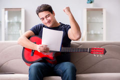 The young man practicing playing guitar at home Royalty Free Stock Photos