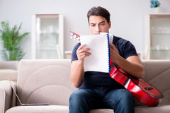 The young man practicing playing guitar at home Stock Photography