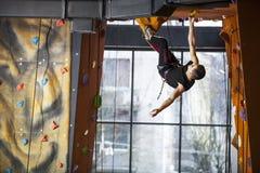 Young man practicing rock-climbing in climbing gym Stock Photos