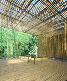 Young man practicing yoga in bamboo house Stock Photo