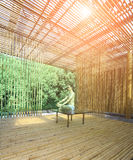 Young man practicing yoga in bamboo house Royalty Free Stock Photography