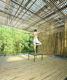 Young man is practicing yoga in bamboo house Royalty Free Stock Image
