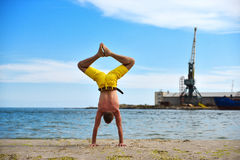 Young man practicing yoga on beach Royalty Free Stock Image