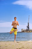 Young man practicing yoga on beach Royalty Free Stock Photography
