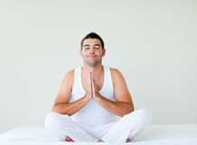 Young man practicing yoga in bed Royalty Free Stock Photos