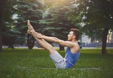 Young man practicing yoga in boat pose outdoors. Young man practicing yoga in boat pose on green grass outdoors, making corner stretching exercise, copy space royalty free stock images