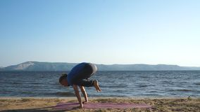 Young man practicing yoga on the coast stock footage