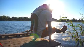 Young man practicing yoga exercise with son on his back on the edge of wooden jetty at lake. Family spending time. Together at nature on summer day. Healthy stock video