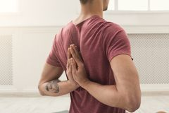 Young man practicing yoga, Reverse Prayer Pose. Young man practicing yoga, making asana exercises. Guy do Reverse Prayer Pose, back and shoulders stretching royalty free stock photography