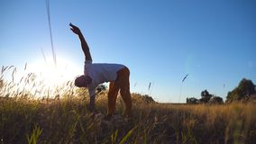 Young man practicing yoga on mat at the field on a sunny day. Sporty guy doing exercise at the meadow. Summer landscape stock footage