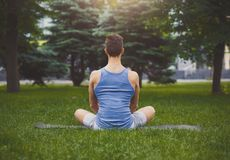 Young man practicing yoga, relax meditation pose. Young man practicing yoga, meditation exercises, back view. Guy does lotus pose for relaxation, sitting on Stock Image