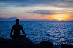 Young man practicing yoga on ocean shore Stock Image