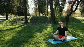 Young Man Practicing Yoga Outdoors At Park Sitting On Mat In Lotus Pose Closed Eyes Meditating. Prores, Slow Motion. 4k stock video footage