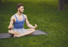 Young man practicing yoga, relax meditation pose. Young man practicing yoga, meditation exercises. Guy does lotus pose for relaxation, sitting on green grass in Royalty Free Stock Photography