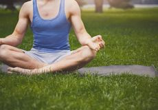 Young man practicing yoga, relax meditation pose. Young man practicing yoga, meditation exercises. Unrecognizable guy does lotus pose for relaxation, sitting on Stock Images