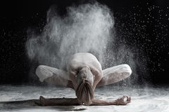 Young man practicing yoga, sitting in Garland exercise with forward bend, variation of Malasana pose. Dynamic asana against a background of white dust Stock Photos
