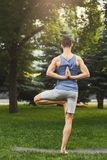 Young man practicing yoga, Reverse Prayer Pose. Young man practicing yoga in tree pose, making asana exercises. Guy do Reverse Prayer Pose, back and shoulders royalty free stock image