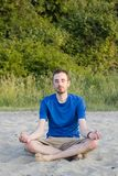 Young man practising yoga on beach Stock Photo