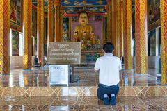 Young man in prayer in front of Buddha, Cambodia Stock Images