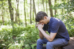 Young man in prayer. A young man in nature with hands folded prayer stock images