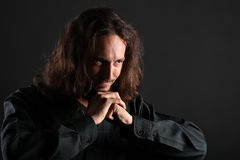 Young man praying. Young guy with long hair and goatee looks somewhere right while praying, isolated on black background Royalty Free Stock Image
