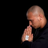 Young man praying. A young asian man with a hoddie is praying over black stock photo