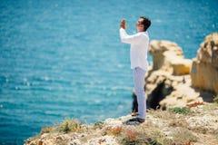 Young handsome Man praying in beautiful inspiring ocean coast enjoy inspirational landscape on rocky top. Young Man praying in beautiful inspiring ocean coast stock photography
