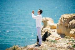 Young handsome Man praying in beautiful inspiring ocean coast enjoy inspirational landscape on rocky top. Young Man praying in beautiful inspiring ocean coast royalty free stock photos