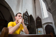 Young man praying in a church. Handsome young man praying in a church stock photos