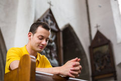 Young man praying in a church. Handsome young man praying in a church royalty free stock photos