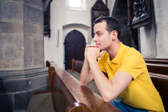 Young man praying in a church Stock Photo