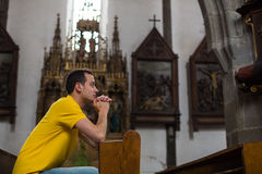 Young man praying in a church Stock Images