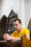 Young man praying in a church Royalty Free Stock Image