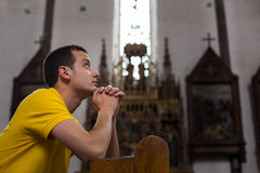 Young man praying in a church Stock Photography