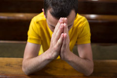 Young man praying in a church. Handsome young man praying in a church royalty free stock photo