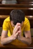 Young man praying in a church