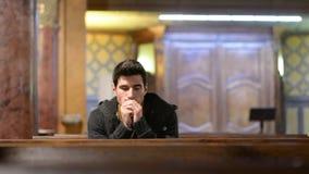 Young man praying in church stock video