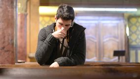 Young man praying in church stock footage