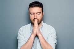 Desperate young man showing clasped hands. Young man praying with hands clasped isolated royalty free stock photography