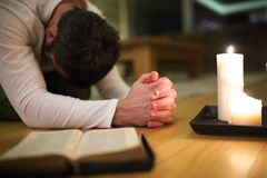 Young man praying, kneeling, Bible and candle next to him. Unrecognizable young man praying, kneeling on the floor, hands clasped together. Bible and burning Royalty Free Stock Photos