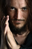 Young man praying and looking into camera. Young guy with long hair looks into camera while praying, face detail Stock Images