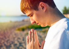 Young Man Praying outdoor. Young Man Praying on the Nature Background closeup royalty free stock image