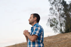 Young man praying. Man standing and praying on a hill outside with his hands clasped together and a tree in the foreground Stock Photos