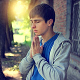Young Man praying. Toned Photo of Young Man praying on the Brick Building Background royalty free stock image