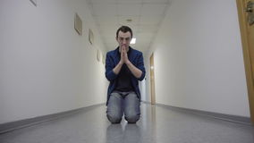 Young man prays kneeling in white corridor stock video footage
